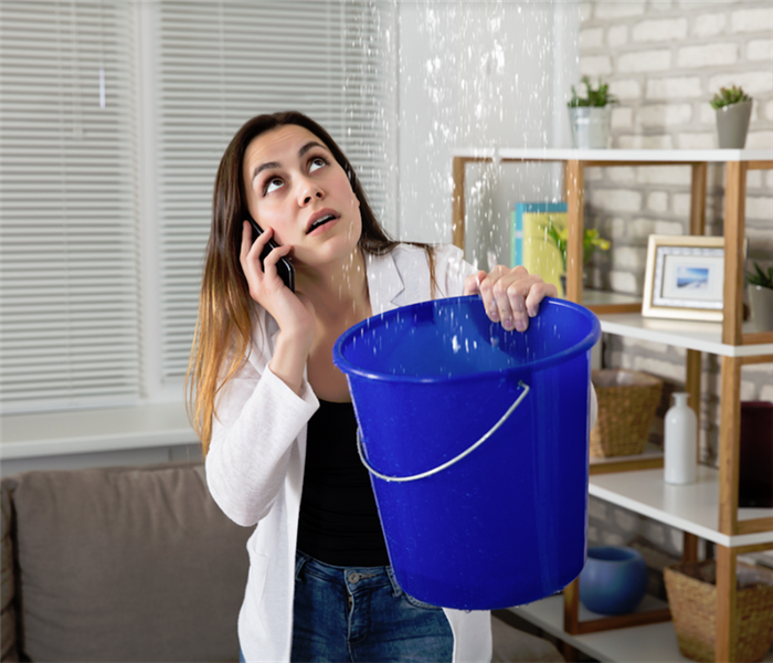 a woman holding a bucket a catch water leaking from her ceiling