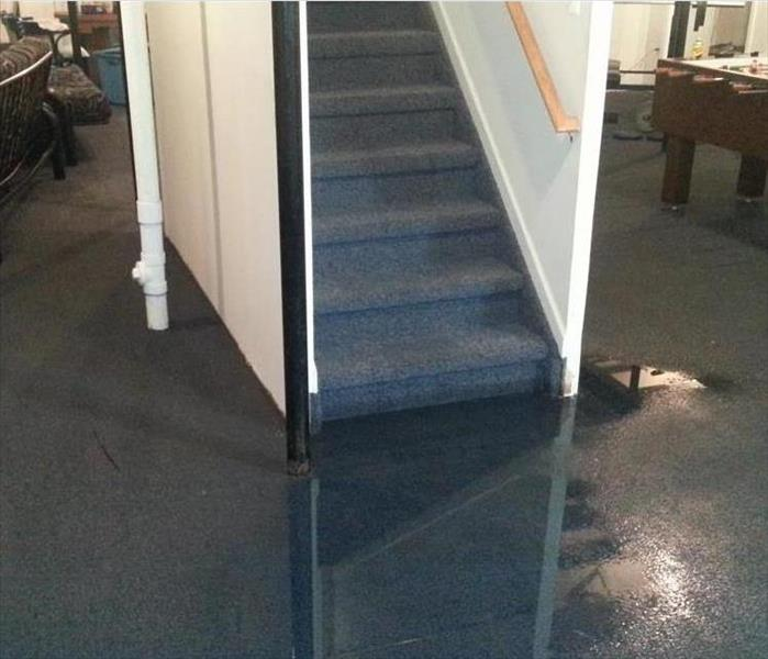 a basement stairwell and carpeted basement that has been flooded