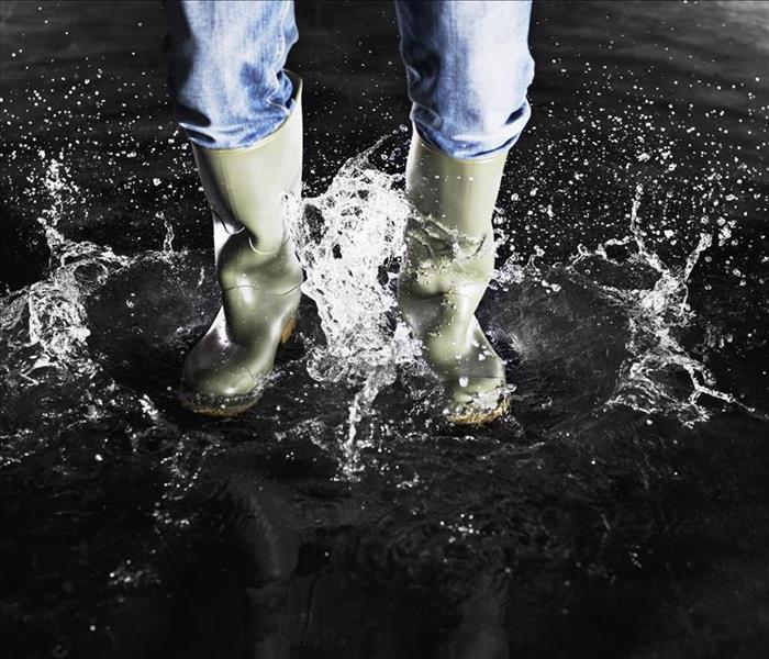 boots splashing in water with person wearing blue jeans
